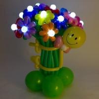 Смайлик, обнимающий светящиеся цветочки.